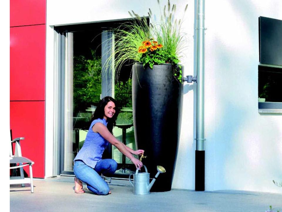 A woman pouring water from the Bullet Rain Barrel with Planter.