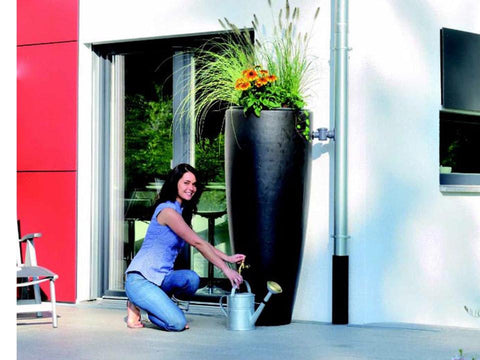 Image of A woman pouring water from the Bullet Rain Barrel with Planter.