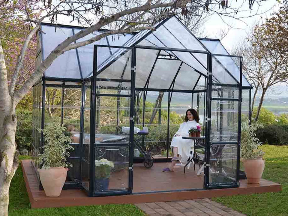 Palram Chalet 12ft x 10ft Hobby Greenhouse HG5400 - full view - open doors- in a garden - a woman sitting inside