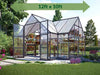 Image of Palram Chalet 12ft x 10ft Hobby Greenhouse HG5400 - full view - with green arrow on top - in a garden