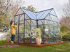 Image of Palram Chalet 12ft x 10ft Hobby Greenhouse HG5400 - in a garden - a woman outside opening the door