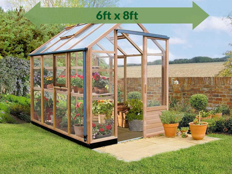 Image of Juliana Classic Greenhouse 6ft x 8ft - open door_green arrow on top showing dimensions - in a garden