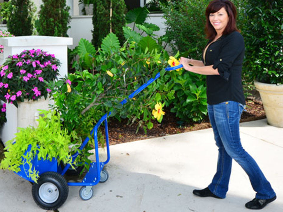 A woman on the right side pulling the blue Potwheelz carrying plants