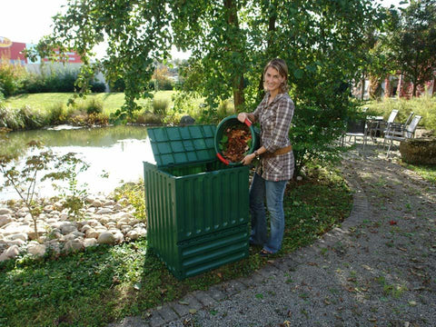 A woman on the right side pouring leaves into Eco King 400 Compost Bin
