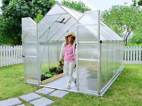 Palram Essence 8ft x 12ft Hobby Greenhouse - HG5812 - full view - in a garden -  open doors with a woman standing inside