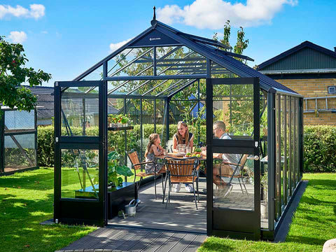 Juliana Premium Greenhouse 9ft x 14ft Anthracite 3mm safety glass with plants inside. Outdoor setting. Front View. Doors are open. Three people inside having a meal.