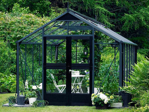 Image of Juliana Premium Greenhouse 9ft x 14ft Anthracite 3mm safety glass with plants inside. Outdoor setting. Front View. Door Closed