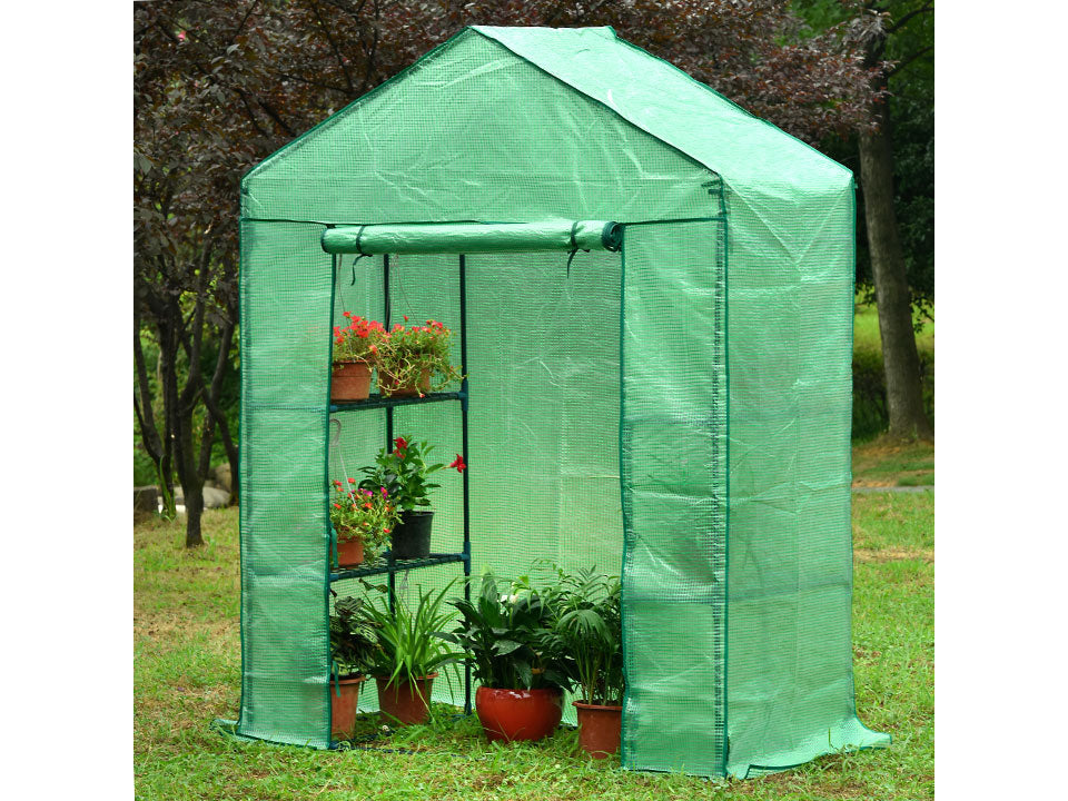 Small green Genesis Portable Walk In Greenhouse with open roll-up door in a garden