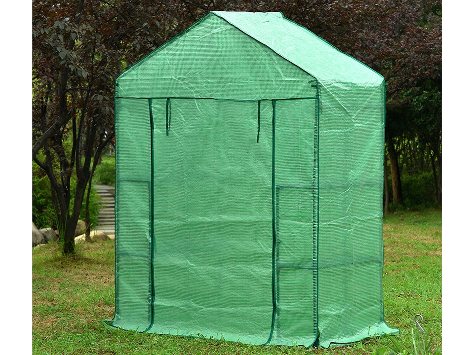 Small green Genesis Portable Walk In Greenhouse with closed roll-up door in a garden