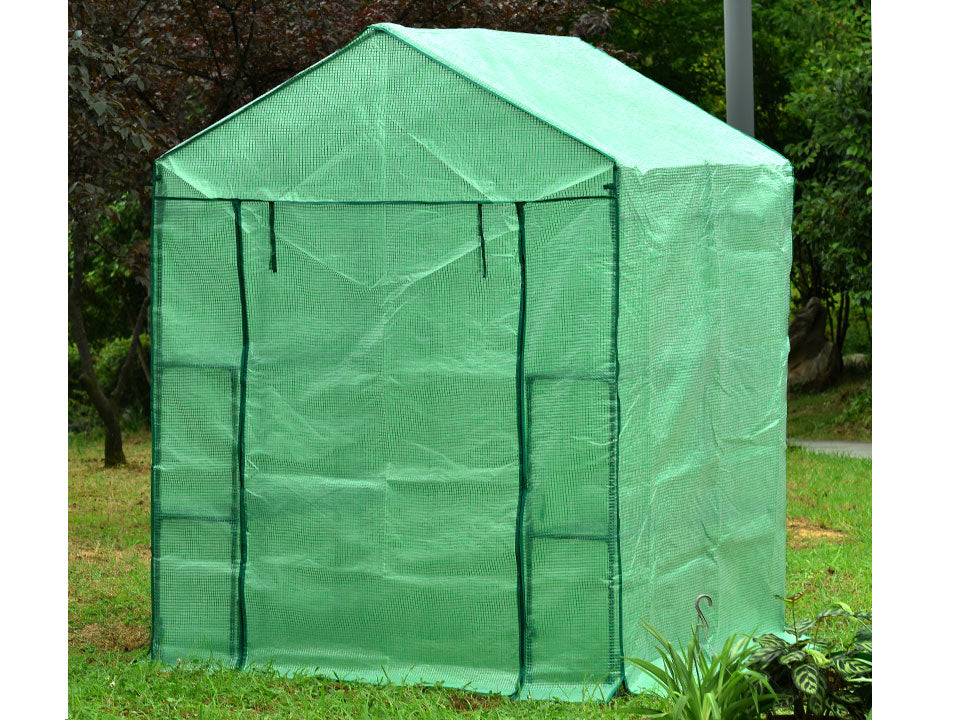 Large green Genesis Portable Walk In Greenhouse with closed roll-up door in a garden