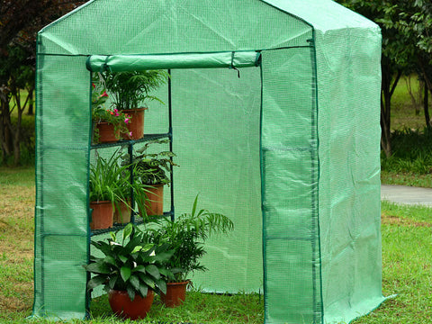Image of Large green Genesis Portable Walk In Greenhouse with open roll-up door in a garden