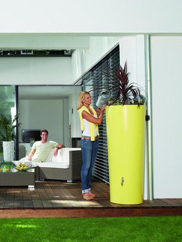 Image of Lemon Yellow High Gloss Rain Barrel & Planter. A woman on the left side watering the plants on top of the barrel.