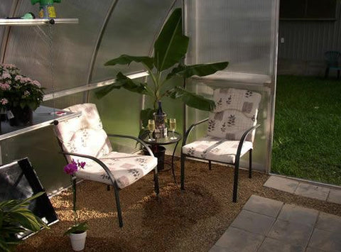 Hoklartherm Riga XL 9 Greenhouse 14x30 corner view with two chairs and a coffee table with a plant in the corner
