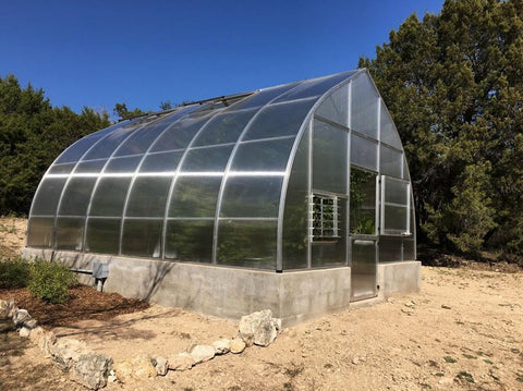 Hoklartherm Riga XL 8 Greenhouse 14x26 set up in a field showing its side view with open door