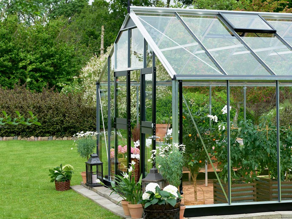 Juliana Gardener Greenhouse 12ft x 19ft - 3mm toughened glass - front and side view - in a garden