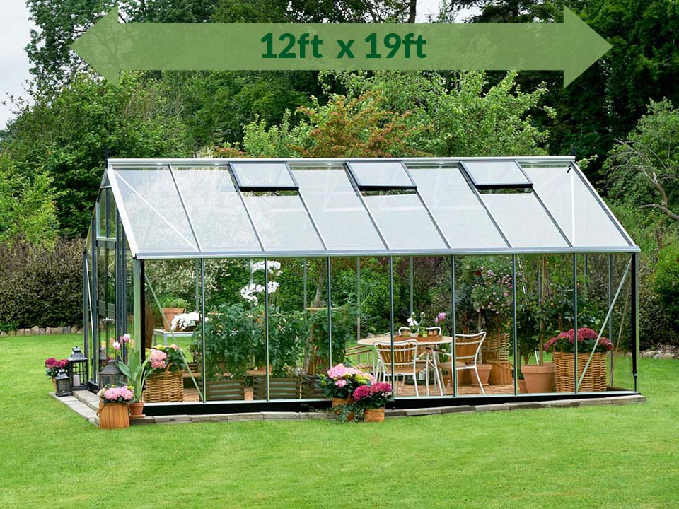 Juliana Gardener Greenhouse 12ft x 19ft - 3mm toughened glass - side view - green arrow on top showing dimensions - in a garden