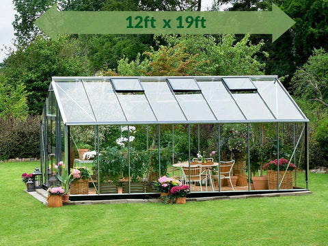 Image of Juliana Gardener Greenhouse 12ft x 19ft - 3mm toughened glass - side view - green arrow on top showing dimensions - in a garden