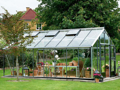 Image of Juliana Gardener Greenhouse 12ft x 19ft - 3mm toughened glass - front and side view - in a garden