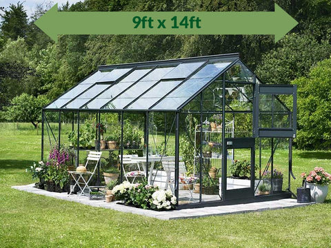Juliana Junior Greenhouse 9ft X 14ft - 3mm glass - in a garden - green arrow on top showing dimensions