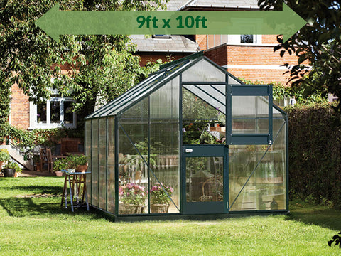 Juliana Junior Greenhouse 9ft x 10ft - in a garden - green arrow on top showing dimensions