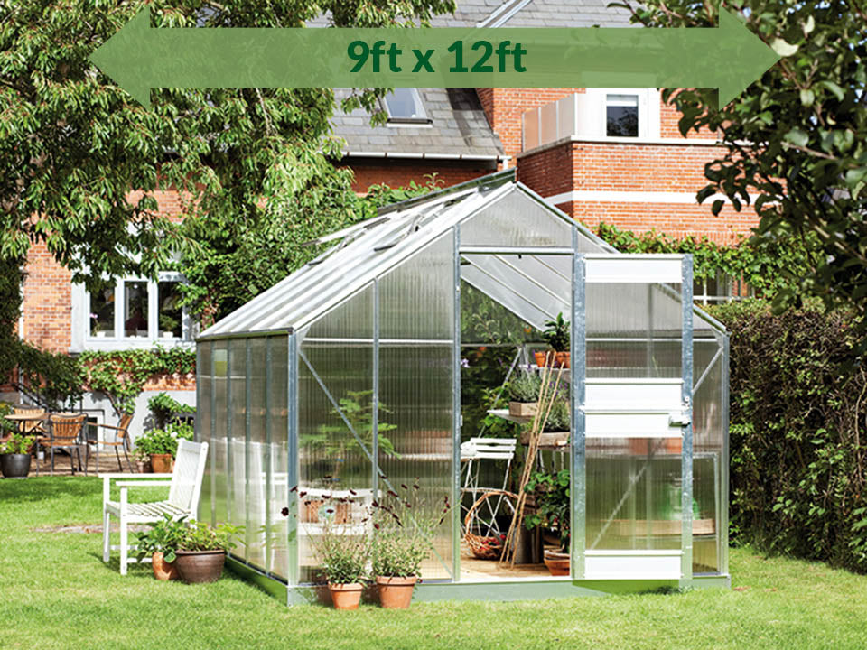Juliana Junior Greenhouse 9ft x 12ft - 6 mm Polycarbonate - in a garden - green arrow with dimension on top