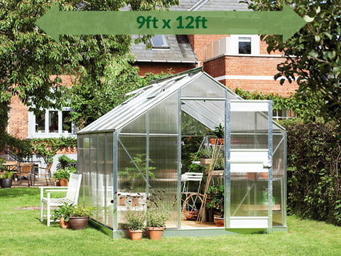 Image of Juliana Junior Greenhouse 9ft x 12ft - 6 mm Polycarbonate - in a garden - green arrow with dimension on top