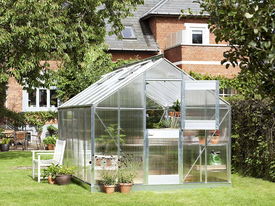 Juliana Junior Greenhouse 9ft x 14ft - Aluminum 6 mm Polycarbonate - open upper part of the door - in a garden