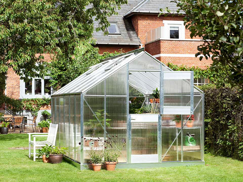 Image of Juliana Junior Greenhouse 9ft x 14ft - Aluminum 6 mm Polycarbonate - open upper part of the door - in a garden