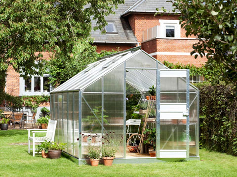 Juliana Junior Greenhouse 9ft x 14ft - Aluminum 6 mm Polycarbonate - double hinged door open - in a garden