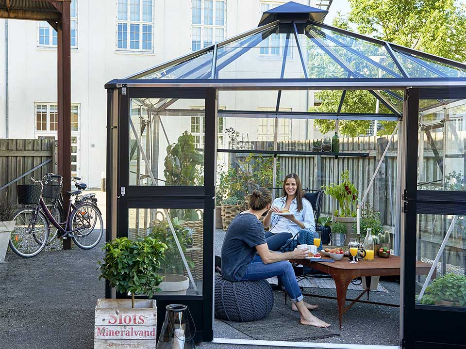 Juliana Oasis Greenhouse 10ft x 10ft Aluminum with two people having meals inside