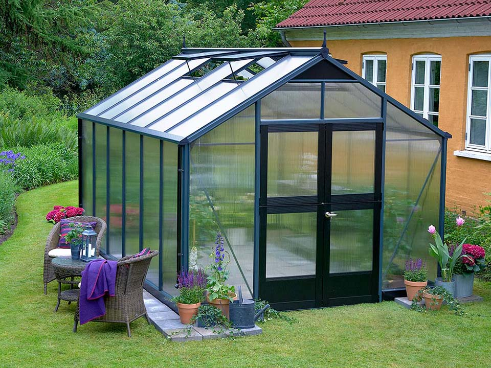 Juliana Premium Greenhouse 9ft x 14ft 10mm Polycarbonate. Left roof windows open. Closed door.