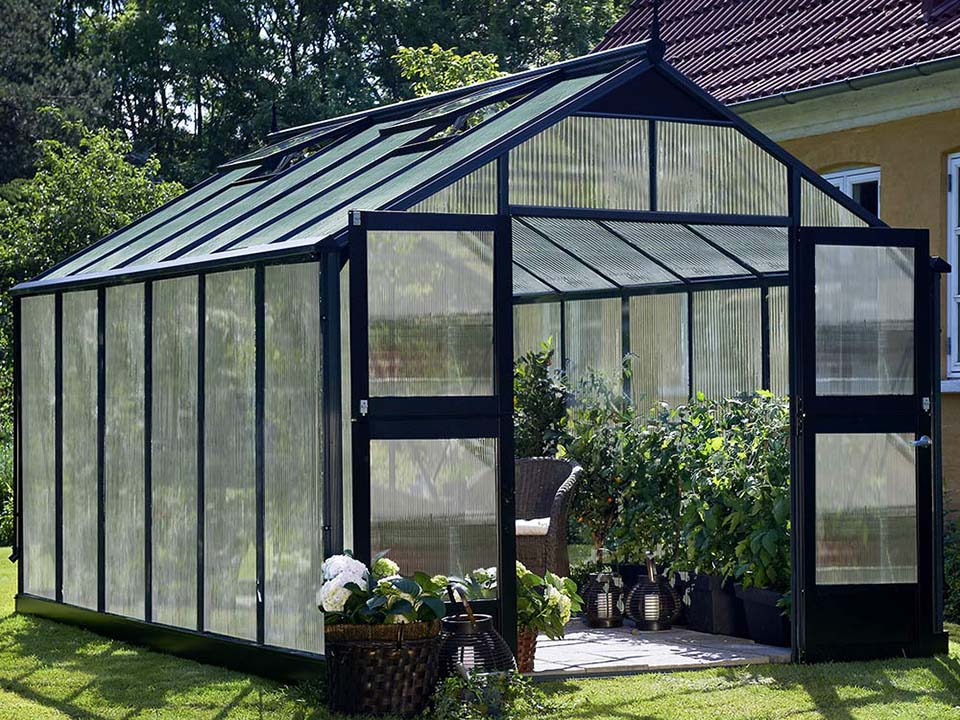 Juliana Premium Greenhouse 9ft x 14ft 10mm Polycarbonate. Left roof windows slightly open. Open doors.