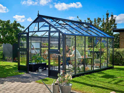 Juliana Premium Greenhouse 9ft x 14ft Anthracite 3mm safety glass with plants inside. Outdoor setting. Side View. Doors are open. Three people inside having a meal.
