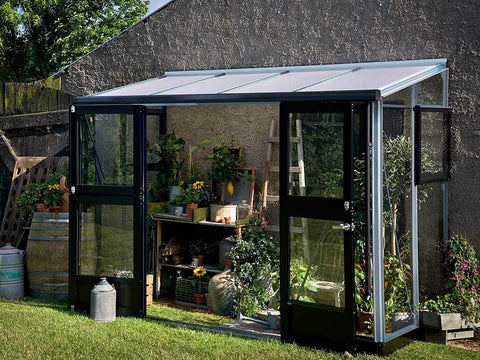 Juliana Veranda Lean-To Greenhouse 10ft x 5ft Aluminum 3mm toughened glass leaning against a wall. Open Doors. With Plants inside.
