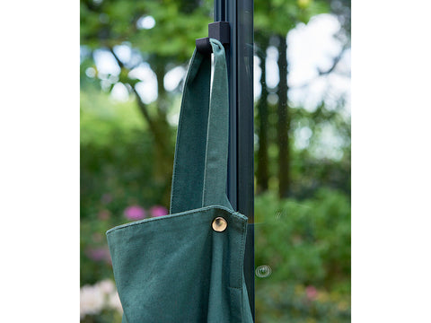 Juliana Greenhouse Frame Hook in a greenhouse with an apron