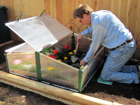 Man planting flowers in the Juwel Easy-Fix Double Cold Frame