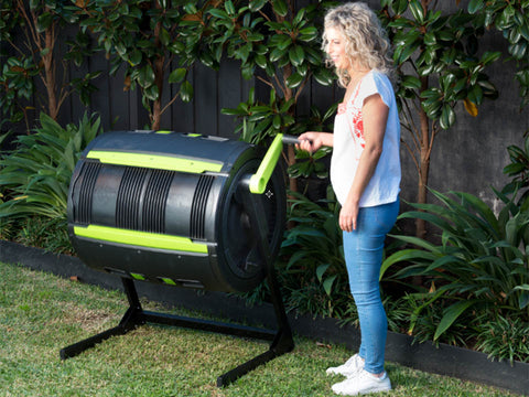 Woman on the right side spinning the MAZE Composter by using the handle