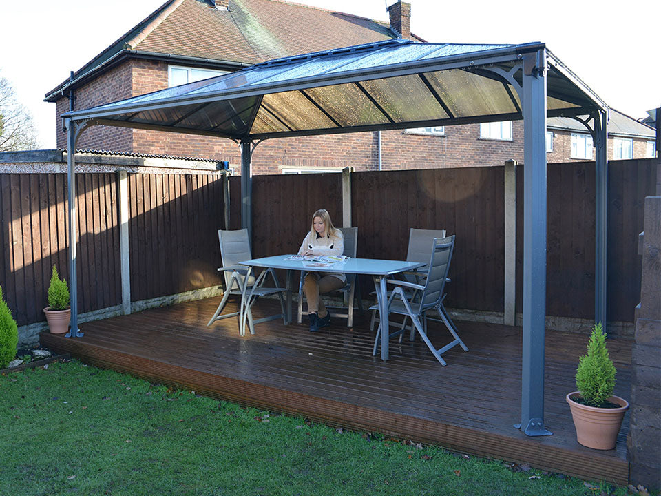 Martinique Hard Top Gazebo with a dining set up in a garden