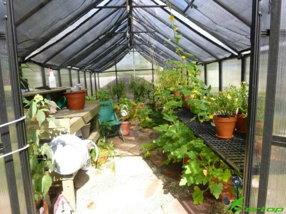 Installed Monticelllo Internal Shade Cloth in a greenhouse with plants and flowers inside