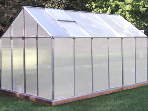 Front and side view of Monticello Growers Edition Greenhouse in a garden with closed door