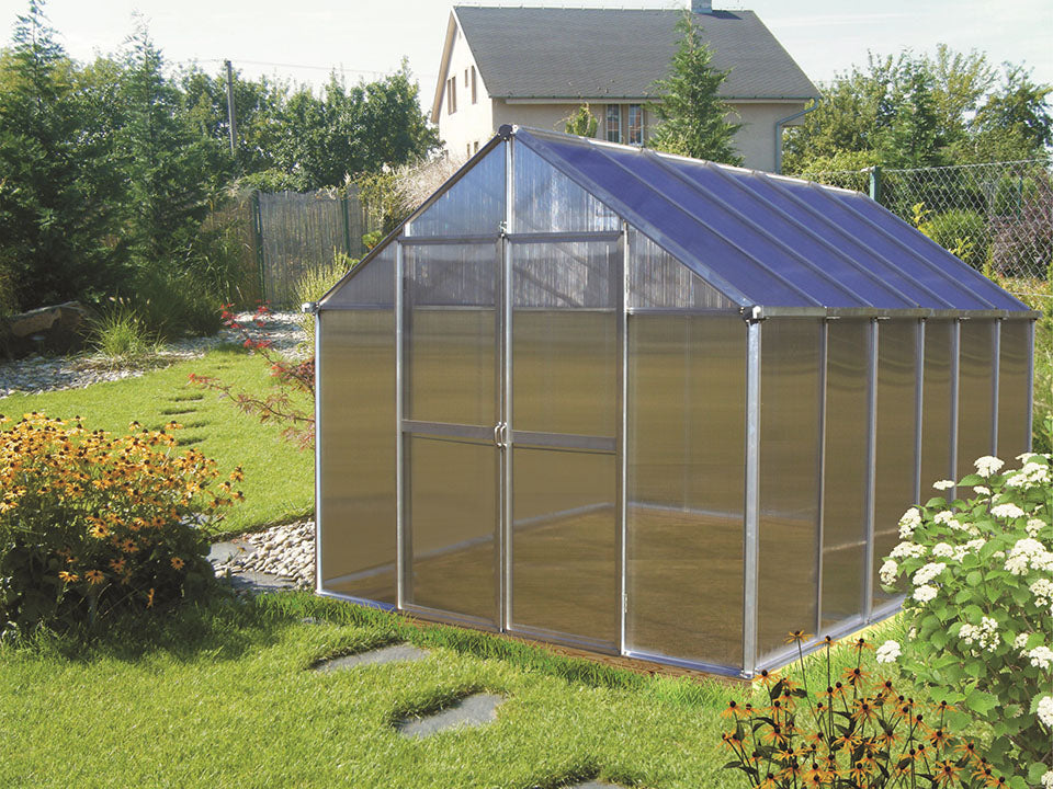 Riverstone Monticello Greenhouse 8x12 with silver frame in a garden