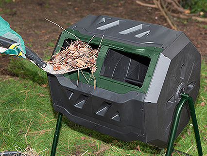 Dropping organic waste into the Mr. Spin Dual Compartment Compost Tumbler with a shovel