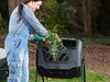 Image of Woman puts organic waste into the Mr. Spin Dual Compartment Compost Tumbler