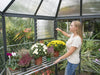 Image of Palram 7ft x 8ft Oasis Hex Greenhouse - HG6000 - interior view - a woman gardening inside the greenhouse