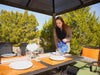 Image of A woman setting up the dining table under Paragon Madrid 10ft x 13ft Hard Top Gazebo