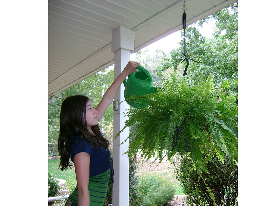 Plant Caddie Hook with a woman on the left side watering her plants