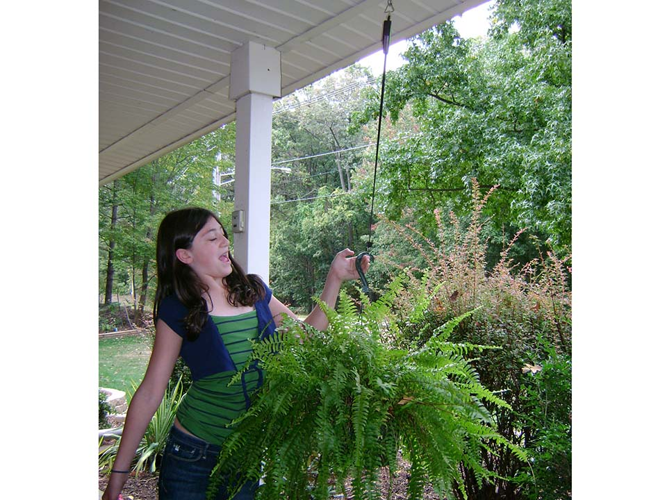 A woman on the left side holding Plant Caddie Hook with Plants