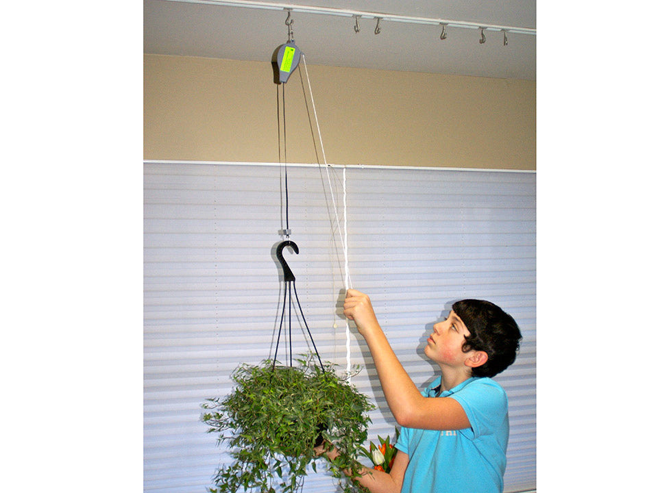 A woman on the right side pulling the pulley of A woman on the left side holding Plant Caddie Hook with Plants
