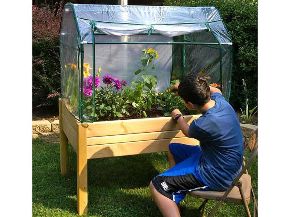 Fully set up Riverstone Eden Mini Greenhouse with a boy sitting by the greenhouse