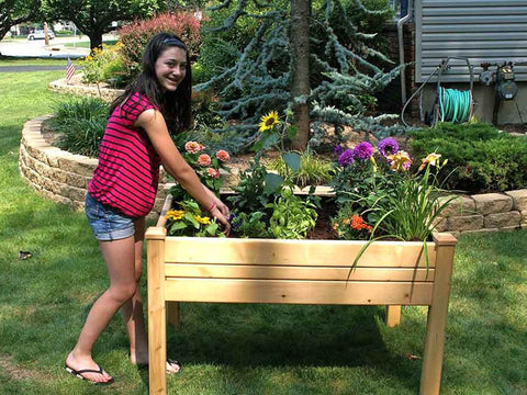 Riverstone Eden Mini Greenhouse - Growing bed -  a girl standing by the growing bed